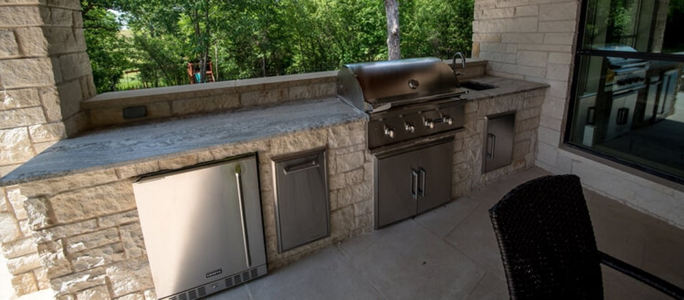 Outdoor kitchen with a built-in fridge, barbeque and sink along with a bar.