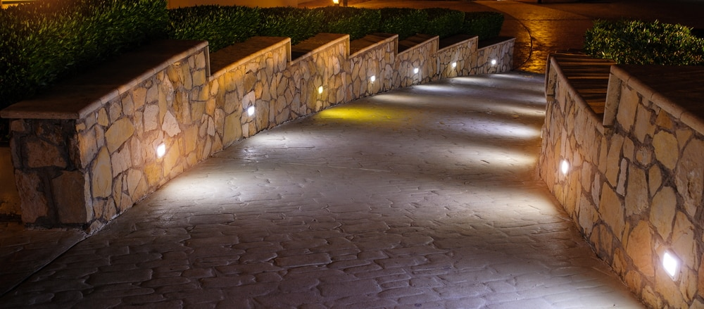 Concrete stone walkway leading to a front door with path lighting.
