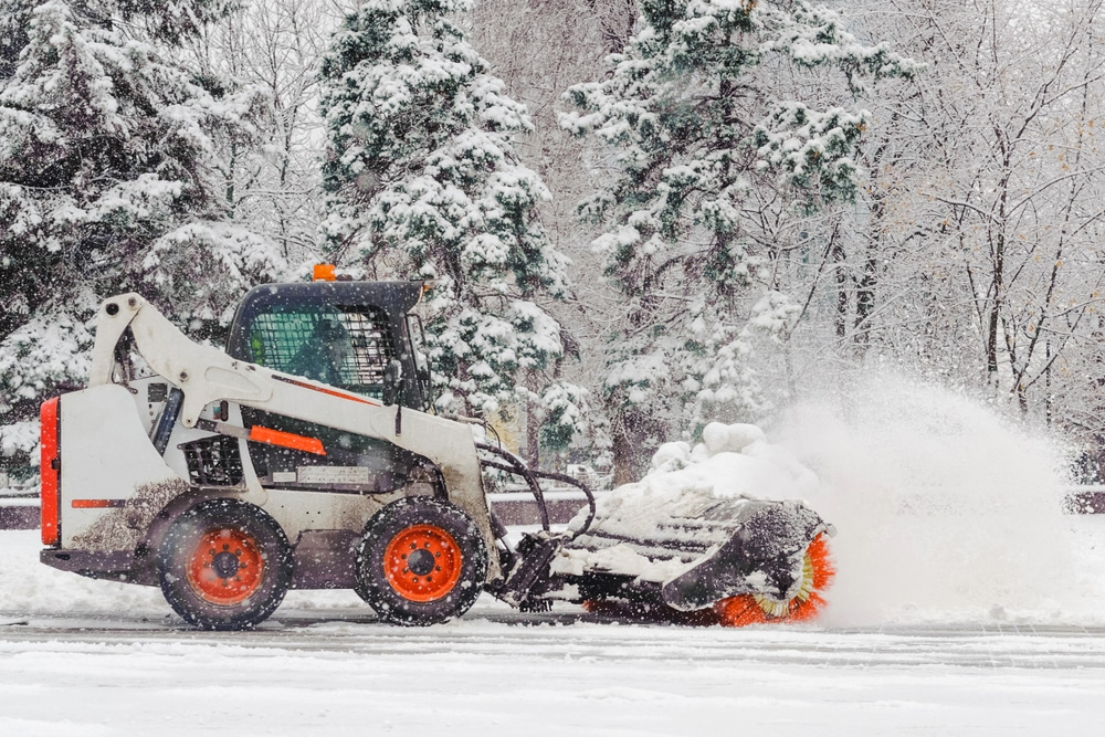Bobcat skid steer with a broom attachment plowing snow at a commercial site in Ottawa, Ontario.