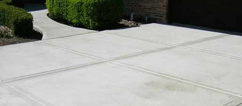 A concrete driveway with multiple grooves and trimmed bushes.