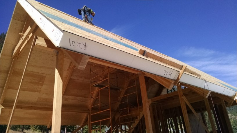 "SIP Roof Installation.  Factory laminated 1/2"" ACX plywood interior finish skin and pre-installed insulated I-joists.  Photo Courtesy of Syndicate Smith LLC"