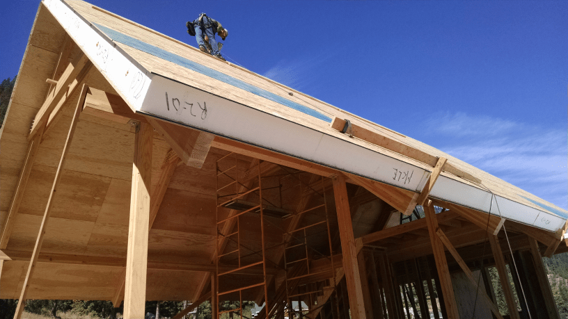 """SIP Roof Installation.  Factory laminated 1/2"""" ACX plywood interior finish skin and pre-installed insulated I-joists.  Photo Courtesy of Syndicate Smith LLC"""