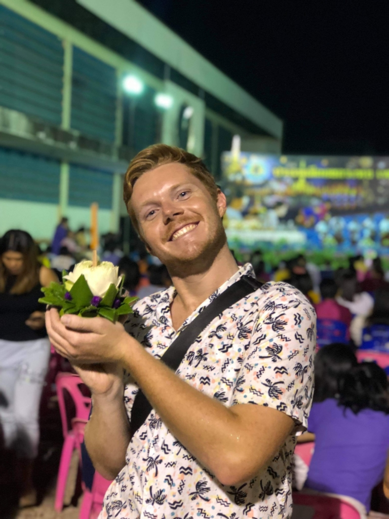 Sean taking a picture with a flower.