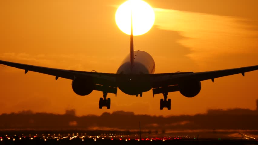 A plane landing while the sun is setting in the background
