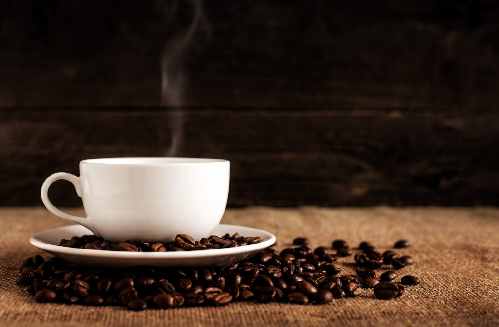 Coffee in a cup and saucer with coffee beans surrounding