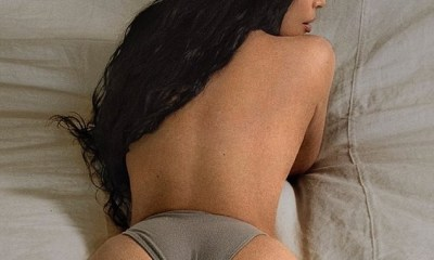 Kim Kardashian flaunts her perky derriere in tiny underwear as she lounges in bed