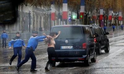 Topless female protester runs at President Trump's motorcade in Paris (photos/video)