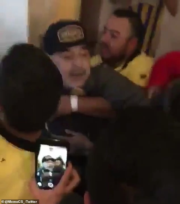Diego Maradona throws a punch at a reporter