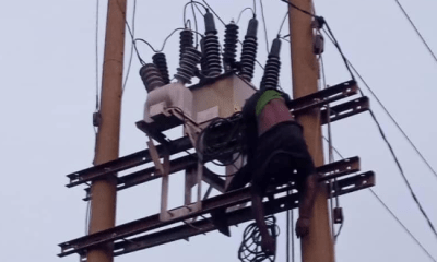 vandal seen hanging from electric pole in Abuja