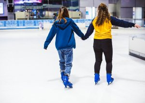 Two girls holding hands while ice skating