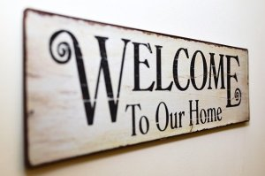 """A wooden sign that says """"Welcome to our home"""""""""""