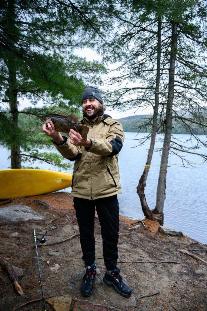 homme qui tient un poisson