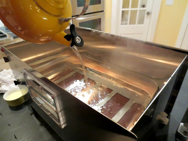 Pouring hot water into a 9x13 pan in HERC Oven