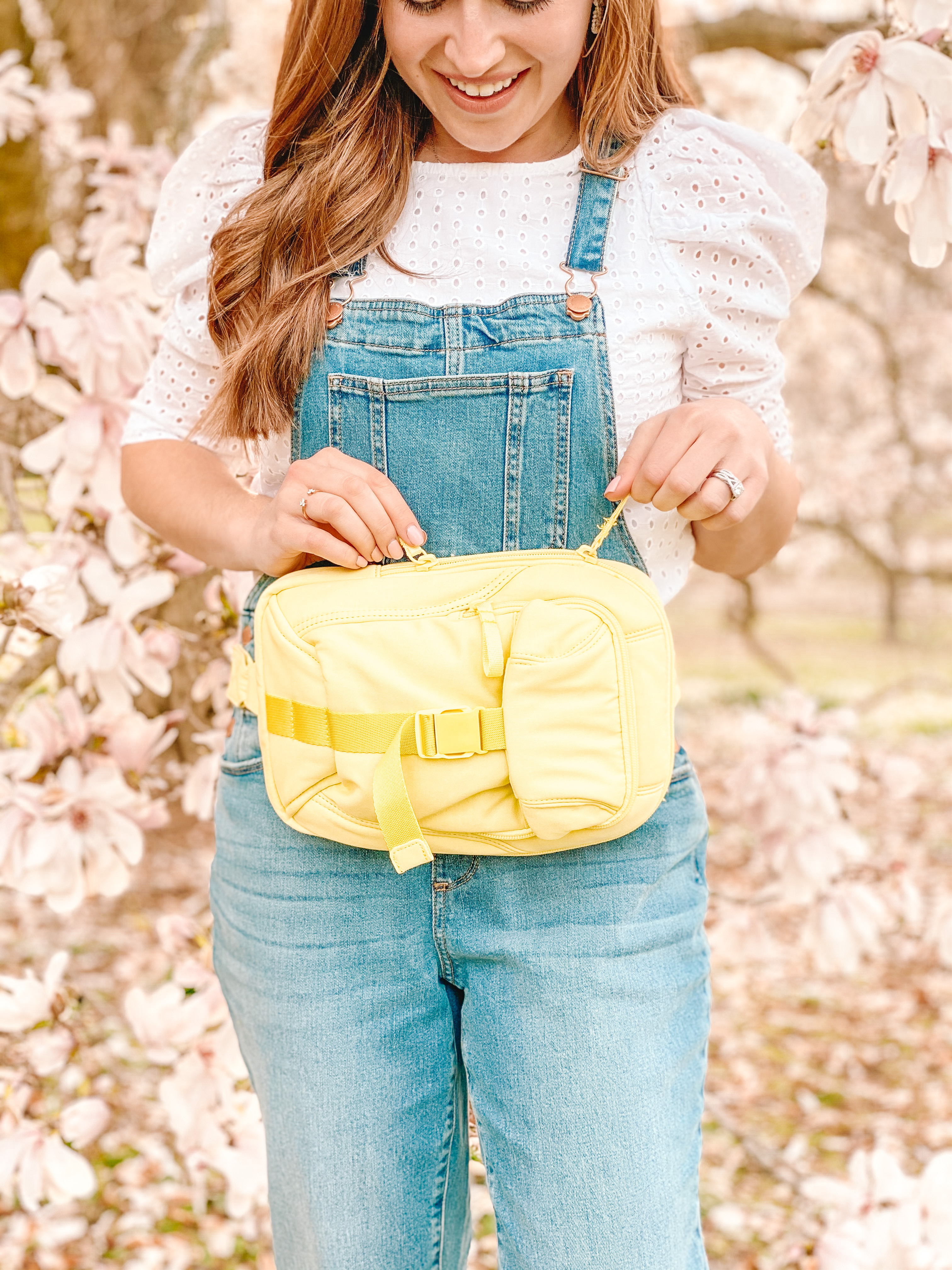 woman stands under magnolia tree with yellow belt bag