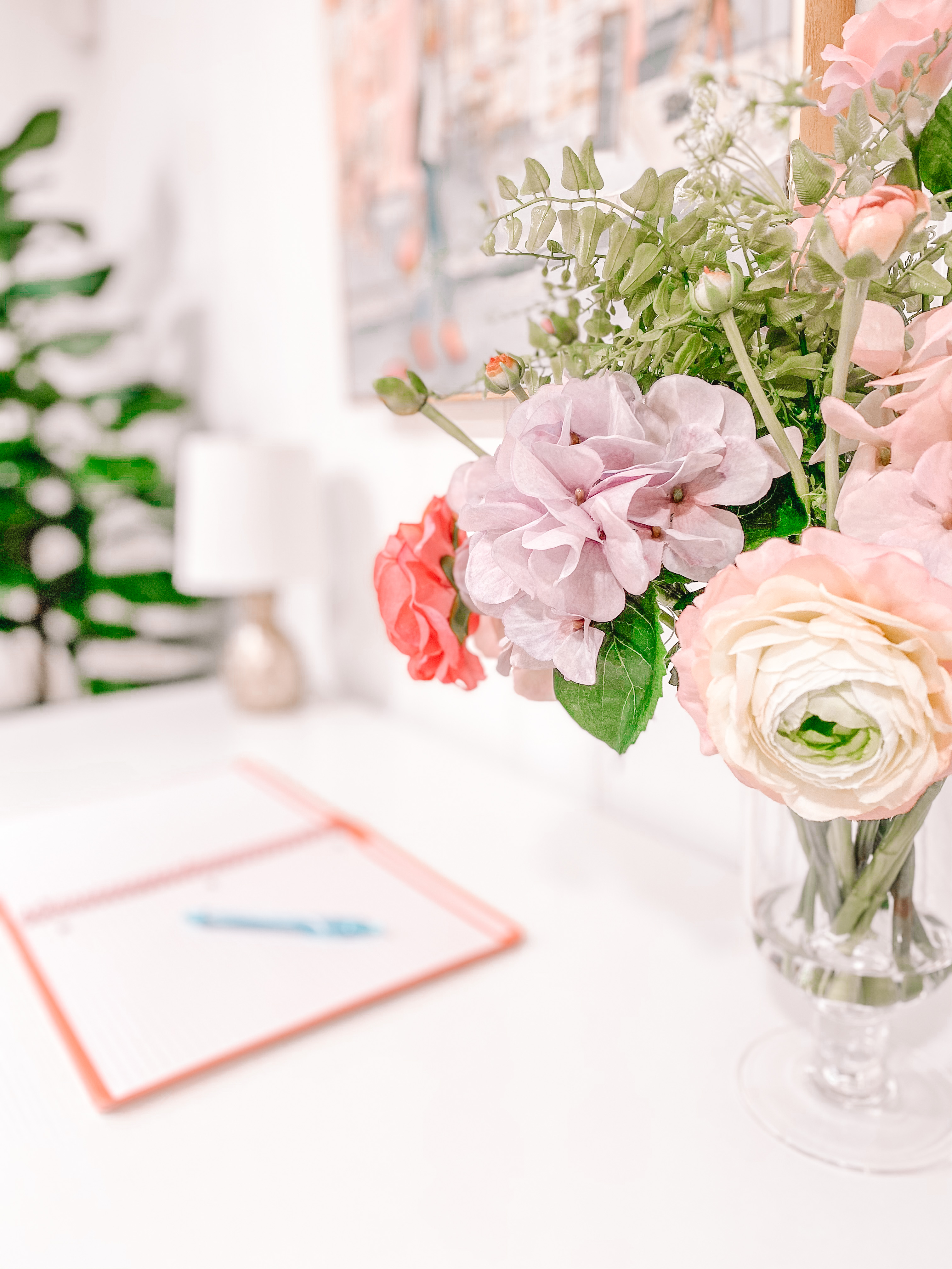fake flowers and notebook on home office desk