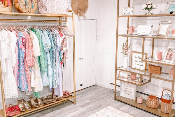 home office and blog room with gold standing clothing rack and colorful clothing, purses, straw hat om the wall and gold standing shelves with photos displayed