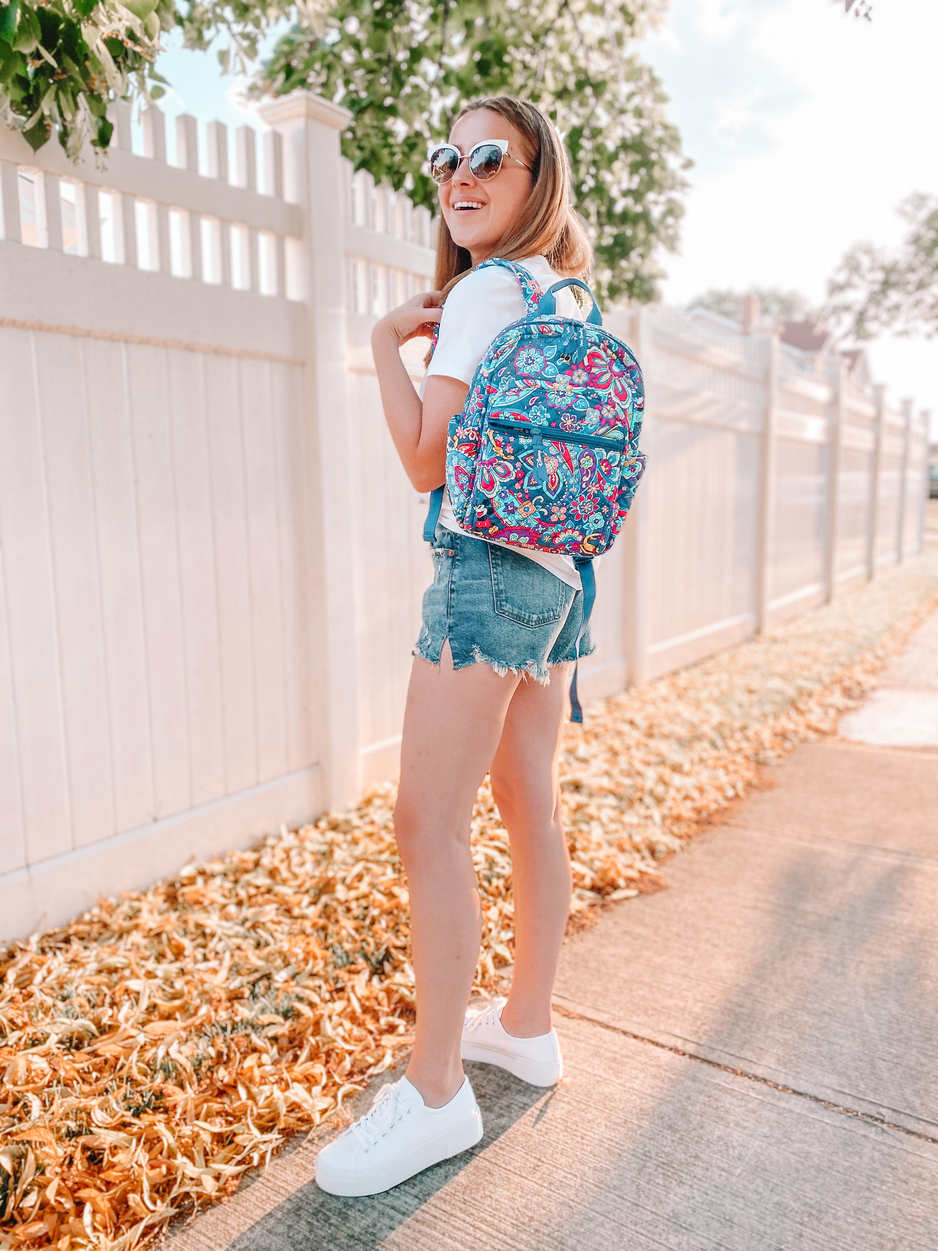 young woman smiles in summer sinshine while holding a vera bradley disney backpack. she has on white platform smeakers, denim shorts, a white tshirt and white sunglasses