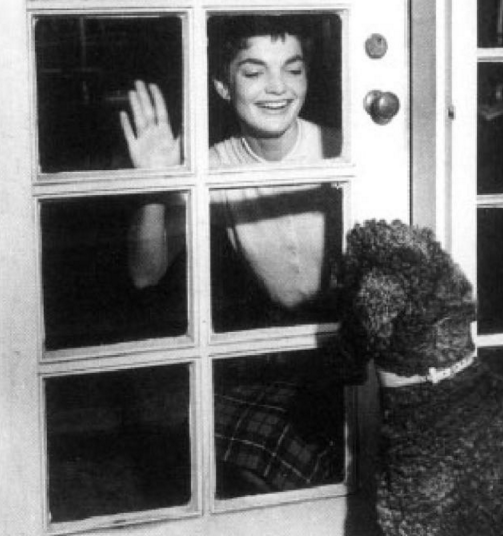 First Lady Jaqueline Kennedy waves to her dog Gaullie through French doors.