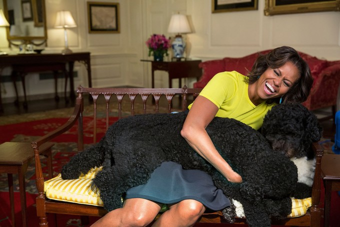 First Lady Michelle Obama hugs family pets Sunny (front), and Bo, April 14, 2014.