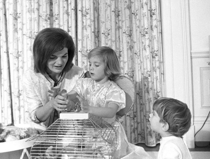 First Lady Jacqueline Kennedy and her children, Caroline and John Jr., play with parakeets Bluebell and Maybelle in John's nursery, Nov. 27, 1962.
