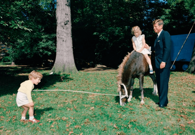 President Kennedy and his kids, John Jr. and Caroline, play with one of their ponies, Leprechaun, September 30, 1963.