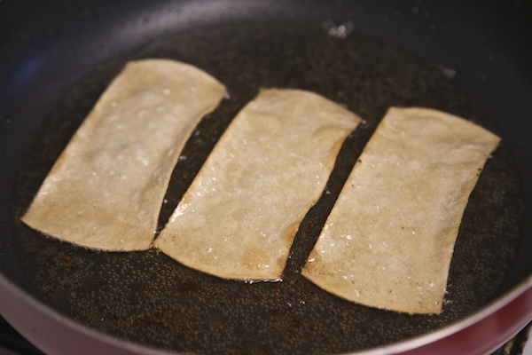 corn tortilla strips frying in oil til crisp