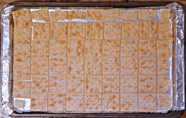 Saltine crackers lined on a cookie sheet for Valentine cracker candy.
