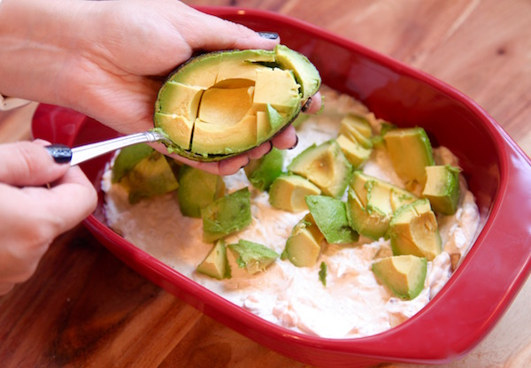 Layer of avocado in cheese dip for Doritos
