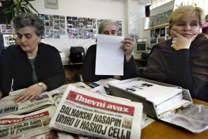 Superstiti del massacro di Srebrenica leggono sui giornali le ultime notizie sulla morte di Slobodan Milosević. Sarajevo marzo 2006 photo Danilo Krstanovic