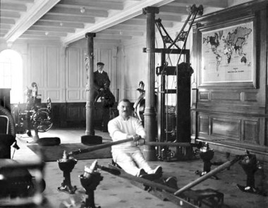 "TW McCawley, ""physical educator"", on the rowing machine, the man behind is Harland and Wolfe electrician William Parr sitting on a mechanical camel. Both men were lost in the disaster."
