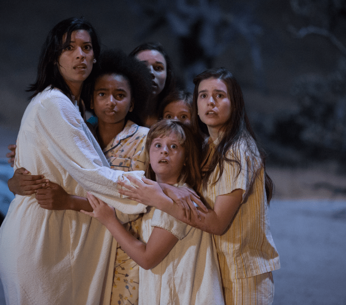 Stephanie Sigman, a woman hugging a group of scared girls.