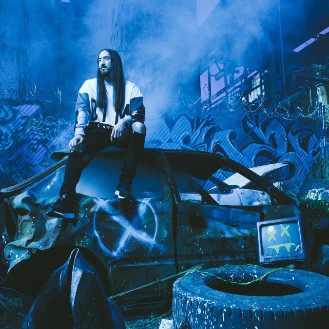 Steve Aoki sits on top of a wrecked car.