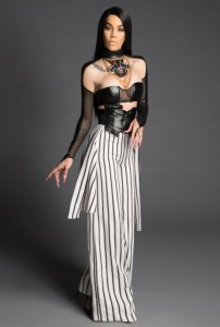 Ivy Queen in a black and white striped jumpsuit.