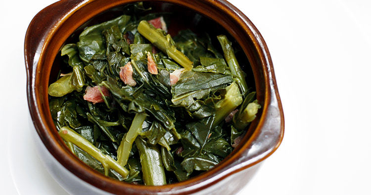 Gourmet homemade collard greens with pieces of ham in a bowl with a white background