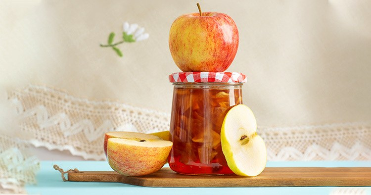 Glass jar of homemade apple jam and apples on kitchen board