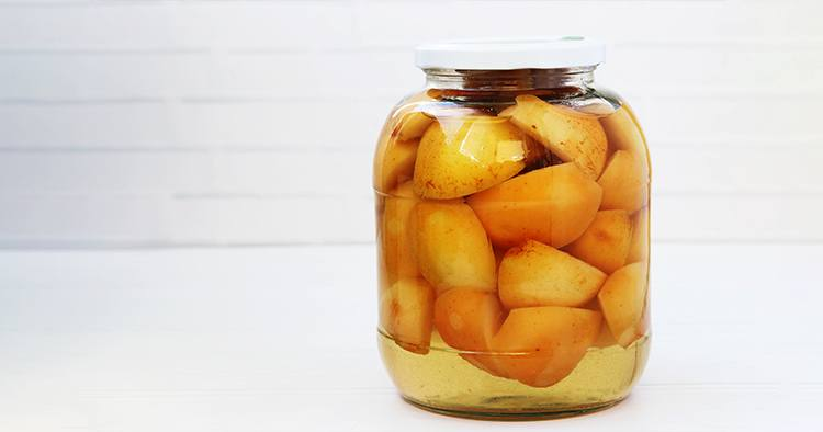 Canned apples in syrup in a jar on a white background.