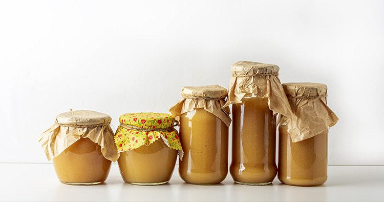 Canned and preserved applesauce in glass jars on white table