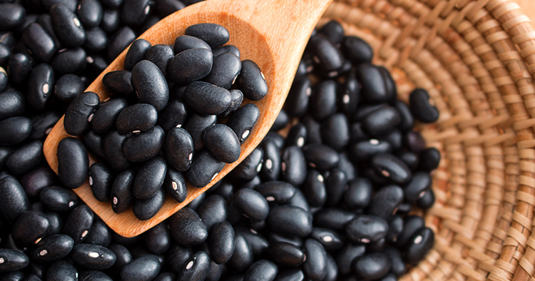 Raw black beans in basket and spoon on wood table.