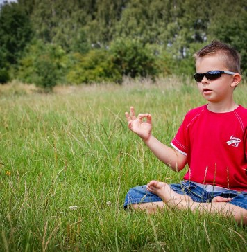 a boy (pragmatic by nature) trying meditation in a field