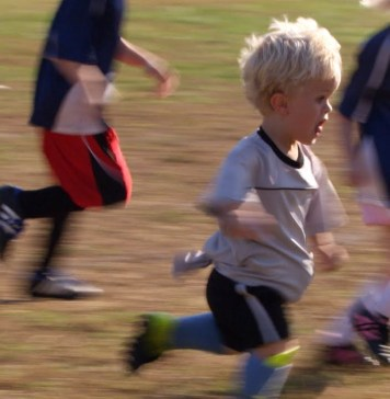 Little kid playing football - striving forward passionately, indicating competitiveness.