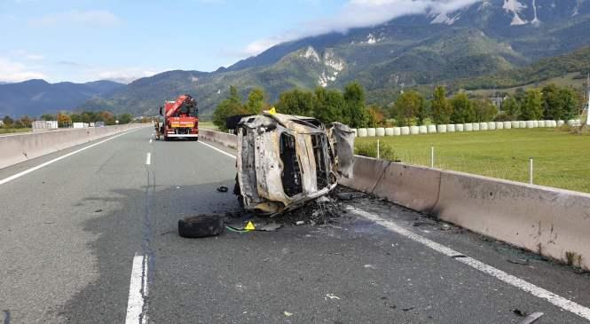 Voznik se je po trčenjih v odbojno ogrado prevrnil, osebni avtomobil pa je zagorel
