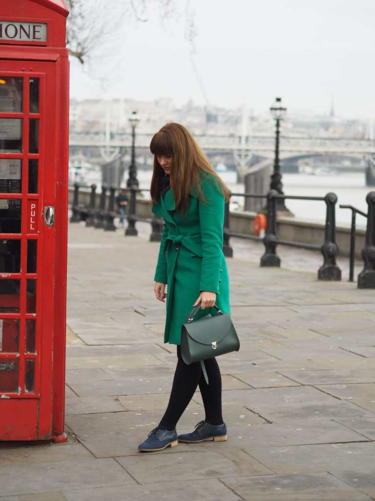 Pretentious Fringe wearing her green coat standing next to a London Red Telephone box with the River Thames in the background.