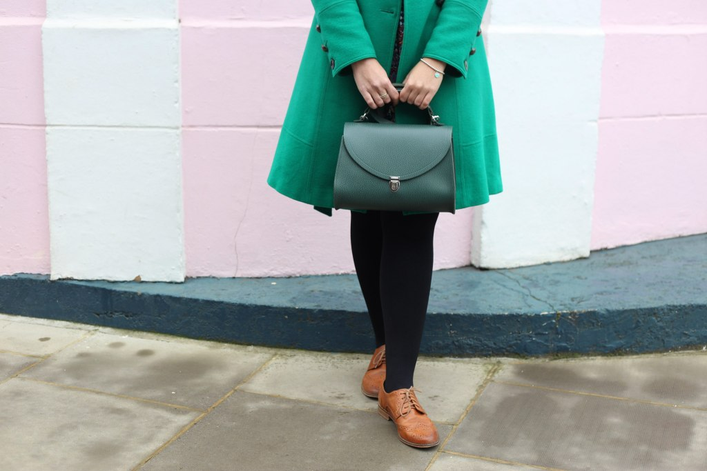 Pretentious Fringe wearing her emerald green coat.  Close up of her holding her cambridge satchel handbag.