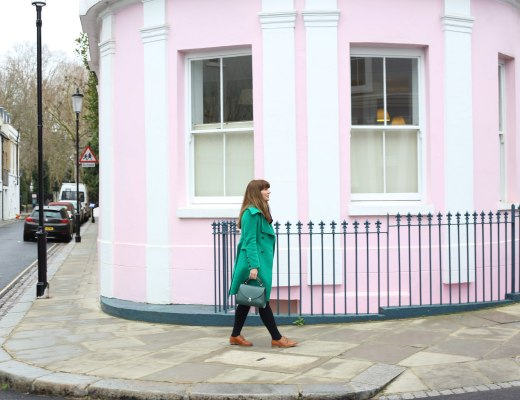 Pretentious Fringe wearing green coat in front of pink building