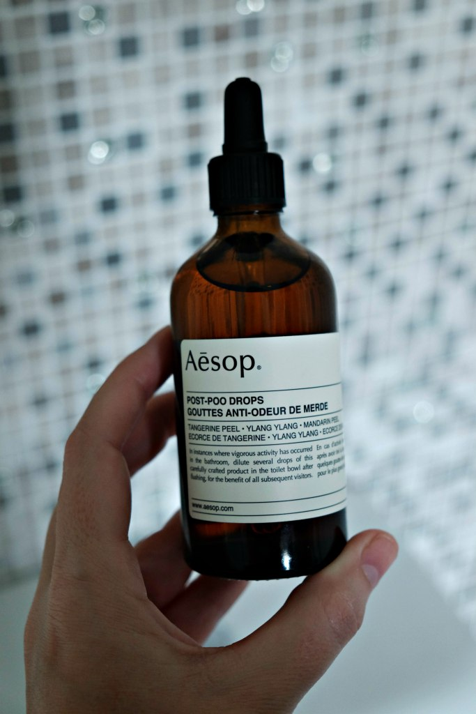 Picture of my hand holding the bottle of Aesop Post Poo drops.