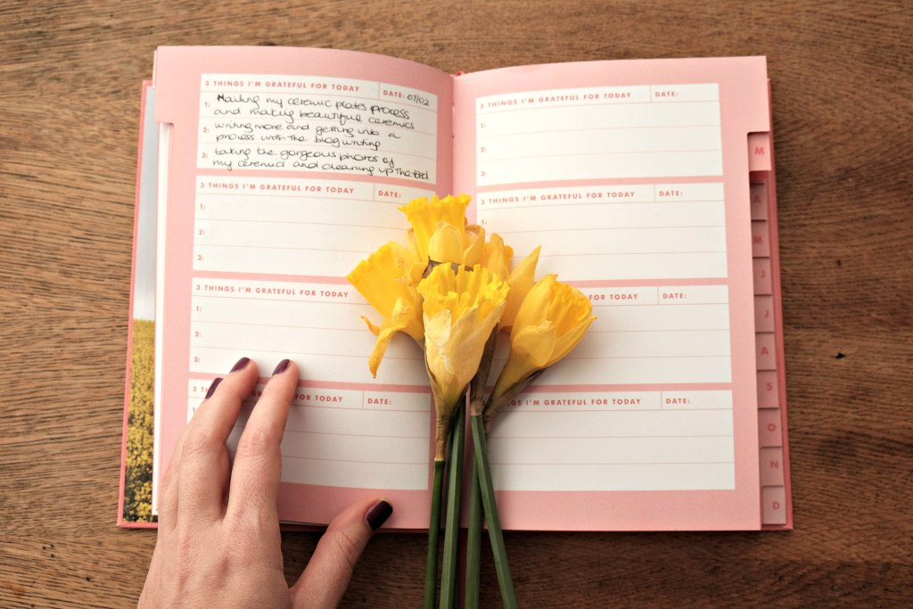 A picture of my gratitude journal open with some enteries and a bunch of daffodils.  My hand is holding the journal open as I couldn't make it stay open with out it!