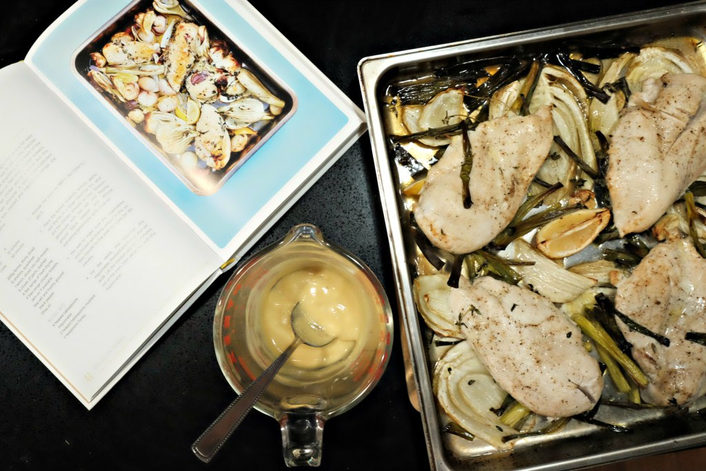 Photo of the finshed chicken and vegetable dish with sauce in a glass jar redy to serve.  The Roasting Tin cook book is open at the page with the recipe.