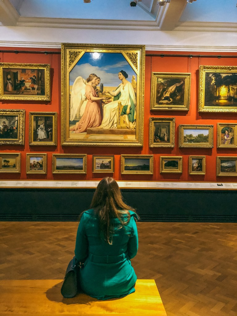 Photo of me sitting in the V&A looking at paintings with my back to the camera.