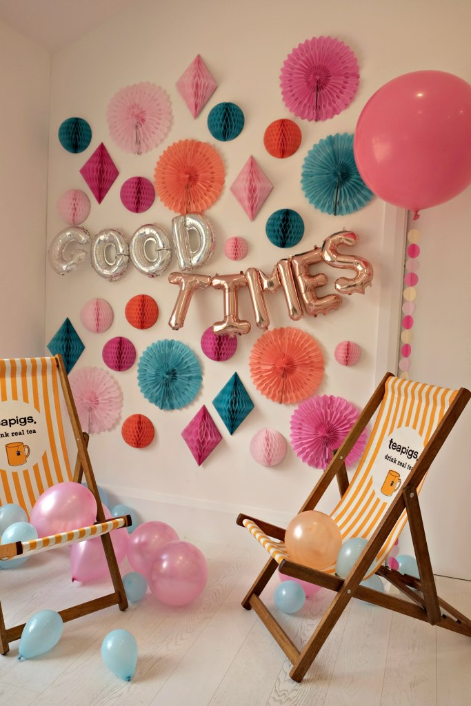 Picture of fabulous wall covered in paper decorations and two teapigs deck chairs in front.  A helium pink balloon is in front with blow up balloons spelling out the words 'good times'. Teapigs Tea School Day.