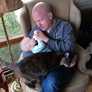 a cat and an infant share a lap